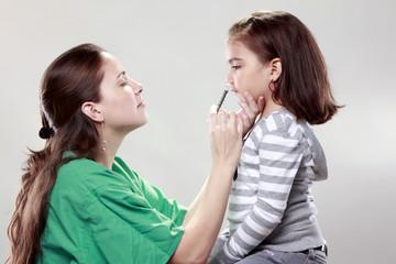 Preteen gets a swine flu shot from her doctor