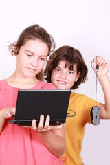 Two attractive sisters with computer on white background
