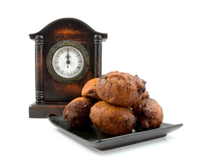 Dutch donut oliebollen and clock over white background
