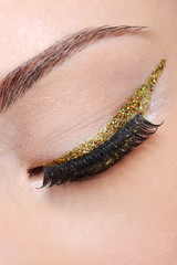 Eye make-up with  golden arrow