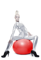 Beautiful cyber woman sitting on a red ball