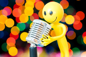 Vintage microphone and smilie against blurred lights
