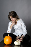 business woman evaluating two pumpkins poster
