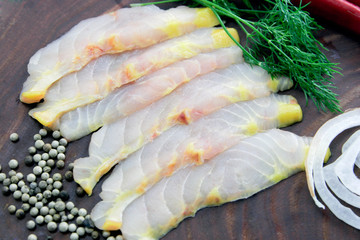 Fresh sturgeon fillet slices decorated on brown cutting board