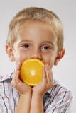 Niño comiendo naranja.