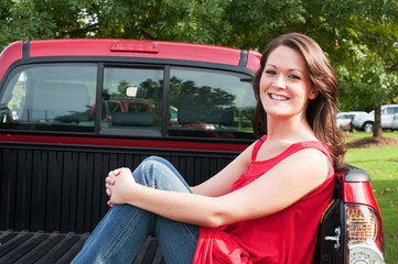 Attractive Brunette Sitting in Bed of Pickup Truck