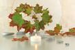 Arrangement mit Kerze, Steinen und Ahornblättern