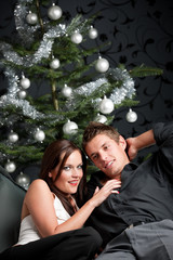 Extravagant man and woman in front of Christmas tree
