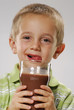 Little boy gesturing and drinking chocolate glass.