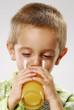 One little boy drinking orange juice