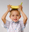 One little boy holding a banana over his head.
