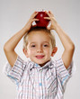 One little boy holding a green apple over his head.