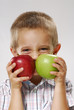 One little boy holding two apples.