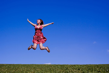 Woman jumping for joy on a green hillside