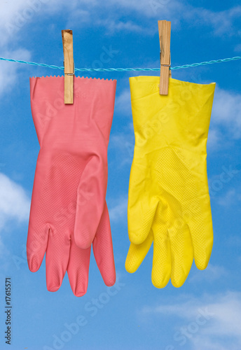 yellow and red gloves drying on rope