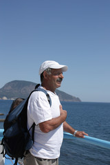 Man with backpack against sea