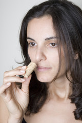 Pretty young woman sniffes on the cork of a wine bottle