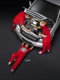 Motor mechanics are working around the car-red