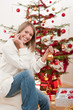 Happy young woman on Christmas in front of tree