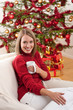 Blond smiling woman in front of Christmas tree