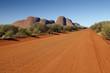 Leinwanddruck Bild - Red dirt road in front of Olgas
