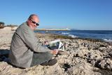 Homme lisant le journal au bord de la mer poster