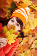 Girl in autumn orange hat on leaf group.Outdoor.