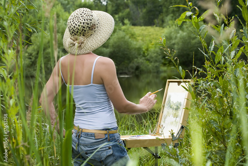 Young woman painting landscape in the open air