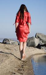 Alone girl walking on the coast