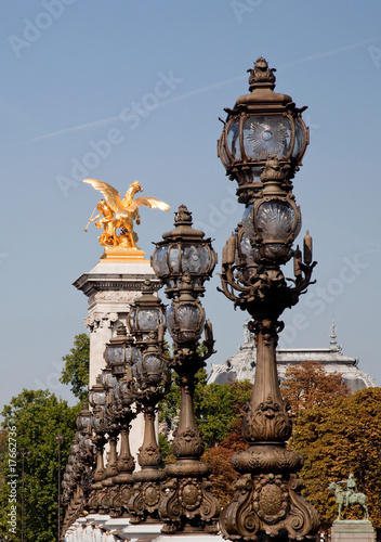 Ornate lamps lead the eye toward golden statue