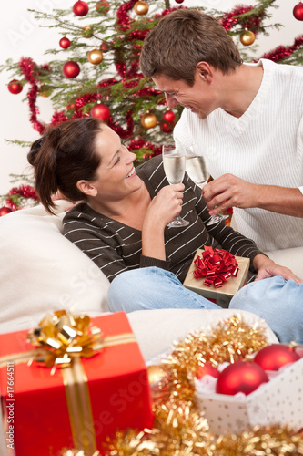 Young couple with champagne in front of Christmas tree
