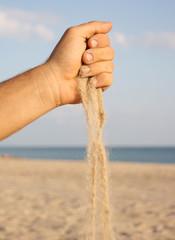 Man's hand  strew sand