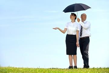 Businessman and businesswoman under umbrella in park