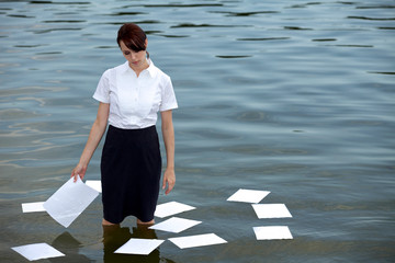 Businesswoman standing in lake with papers floating on water