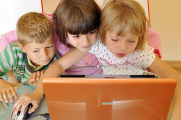 Three children playing on computer