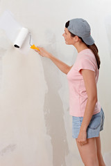 Young woman decorate wall with white paint