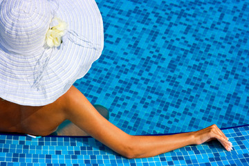 Woman with white hat in swimming pool