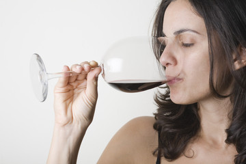 Pretty young woman drinking red wine