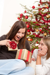 Two smiling women unpacking Christmas present