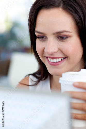 Beautiful businesswoman in office drinking coffee