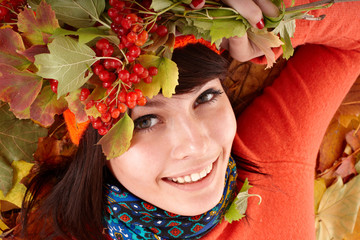 Girl in autumn orange hat on leaf group and berry.