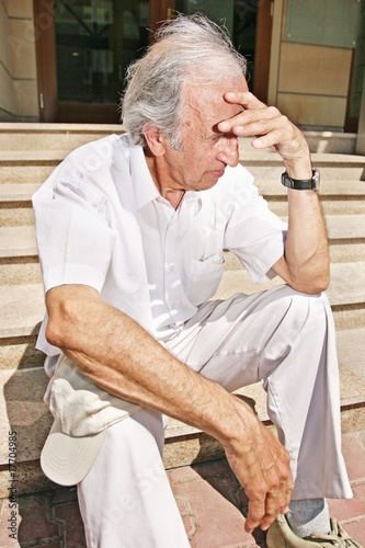 grey-haired, old man sitting on stairs on a summer day
