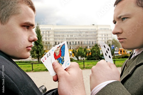 two men playing cards on a street
