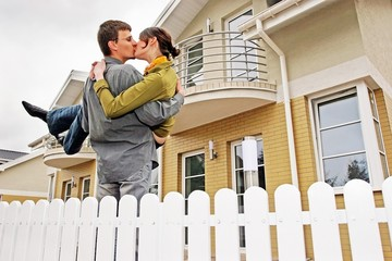 couple in front of one-family house in modern residential area.