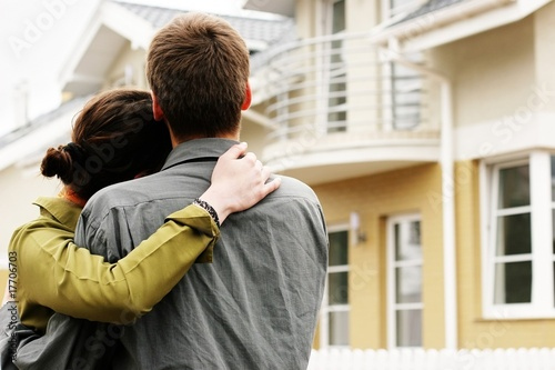 couple in  front of one-family house