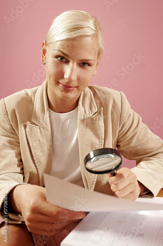 work environment- woman over some paperwork on pink