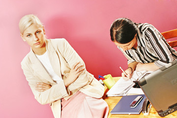 businesswoman and a secretary in modern office-on pink