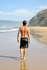 Young healthy guy making a walk along the atlantic ocean