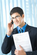 Happy businessman with cellphone and documents at office