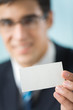 Happy businessman showing business card at office